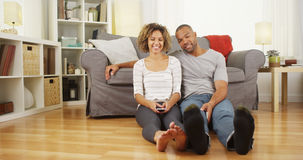 Cute African couple sitting on floor in living room Stock Photography
