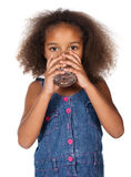 Cute african girl. Adorable cute african child with afro hair wearing a denim dress. The girl is drinking water from a clear glass Stock Images