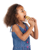Cute african girl. Adorable cute african child with afro hair wearing a denim dress. The girl is holding a big choc chip cookie Stock Image