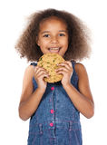 Cute african girl. Adorable cute african child with afro hair wearing a denim dress. The girl is holding a big choc chip cookie Stock Photo