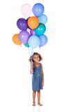 Cute african girl. Adorable cute african child with afro hair wearing a denim dress. The girl is holding a bunch of bright coloured helium balloons Stock Images