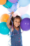 Cute african girl. Adorable cute african child with afro hair wearing a denim dress. The girl is holding a bunch of bright coloured helium balloons Stock Photo