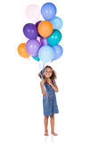 Cute african girl. Adorable cute african child with afro hair wearing a denim dress. The girl is holding a bunch of bright coloured helium balloons Stock Photos