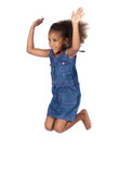 Cute african girl. Adorable cute african child with afro hair wearing a denim dress. The girl is jumping and smiling Royalty Free Stock Photo