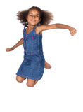 Cute african girl. Adorable cute african child with afro hair wearing a denim dress. The girl is jumping and smiling Stock Image