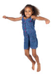 Cute african girl. Adorable cute african child with afro hair wearing a denim dress. The girl is jumping and smiling Royalty Free Stock Image