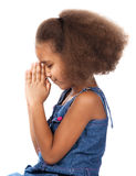Cute african girl. Adorable cute african child with afro hair wearing a denim dress. The girl is kneeling and praying Royalty Free Stock Photo