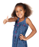 Cute african girl. Adorable cute african child with afro hair wearing a denim dress. The girl is showing a thumbs up to the camera Stock Photo