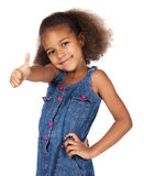 Cute african girl. Adorable cute african child with afro hair wearing a denim dress. The girl is showing a thumbs up to the camera Royalty Free Stock Image