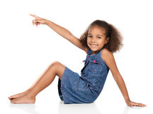 Cute african girl. Adorable cute african child with afro hair wearing a denim dress. The girl is sitting and pointing away from the camera Royalty Free Stock Photography