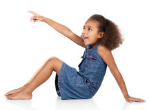 Cute african girl. Adorable cute african child with afro hair wearing a denim dress. The girl is sitting and pointing away from the camera Stock Photos