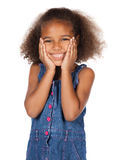 Cute african girl. Adorable cute african child with afro hair wearing a denim dress. The girl is standing and smiling at the camera Royalty Free Stock Photography