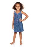 Cute african girl. Adorable cute african child with afro hair wearing a denim dress. The girl is standing and smiling at the camera Stock Images
