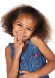 Cute african girl. Adorable cute african child with afro hair wearing a denim dress. The girl is standing and smiling at the camera Royalty Free Stock Images