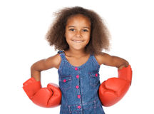 Cute african girl. Adorable cute african child with afro hair wearing a denim dress. The girl is wearing big red boxing gloves Stock Images