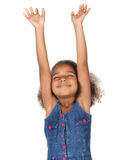 Cute african girl. Adorable cute african child with afro hair wearing a denim dress. The girl is worshipping with her hands lifted up Royalty Free Stock Photos