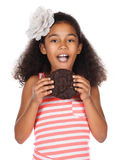 Cute african girl. Adorable cute african child with afro hair wearing a white and pink striped dress. The girl is holding a big choc chip cookie Stock Photo