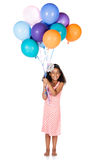 Cute african girl. Adorable cute african child with afro hair wearing a white and pink striped dress. The girl is holding a bunch of bright coloured helium Stock Image