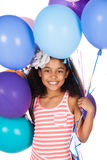 Cute african girl. Adorable cute african child with afro hair wearing a white and pink striped dress. The girl is holding a bunch of bright coloured helium Royalty Free Stock Photo
