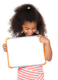 Cute african girl. Adorable cute african child with afro hair wearing a white and pink striped dress. The girl is holding a small white board Stock Photo