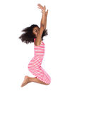 Cute african girl. Adorable cute african child with afro hair wearing a white and pink striped dress. The girl is jumping and smiling Stock Photography