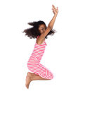 Cute african girl. Adorable cute african child with afro hair wearing a white and pink striped dress. The girl is jumping and smiling Royalty Free Stock Photography