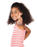 Cute african girl. Adorable cute african child with afro hair wearing a white and pink striped dress. The girl is showing a thumbs up to the camera Royalty Free Stock Image