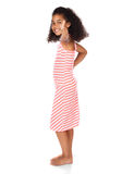 Cute african girl. Adorable cute african child with afro hair wearing a white and pink striped dress. The girl is showing a thumbs up to the camera Royalty Free Stock Images