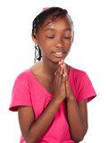 Cute african girl. Adorable small african child with braids wearing a bright pink shirt. The girl is kneeling and praying Stock Images