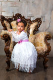 Cute african  girl with curly hair in a white lace dress on vintage chair.  Stock Images