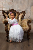 Cute african  girl with curly hair in a white lace dress on vintage chair.  Stock Photo