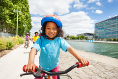 Cute African girl cycling along river embankment stock photo