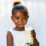 Cute african girl drinking glass of milk. Stock Photography