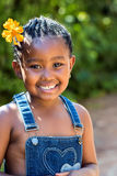 Cute african girl with flower in hair. Royalty Free Stock Images