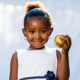 Cute african girl holding apple. Close up portrait of cute African girl holding apple in hand. against light background Stock Photography