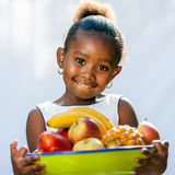 Cute african girl holding fruit bowl. Royalty Free Stock Photo