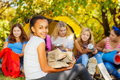 Cute African girl holding kindling wood sitting. Near bonfire at camping with her friends Royalty Free Stock Photography