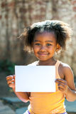 Cute african girl holding white blank card. Royalty Free Stock Images