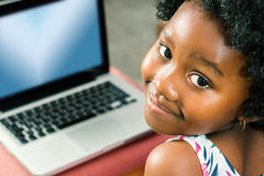 Cute african girl with laptop in background. royalty free stock photo