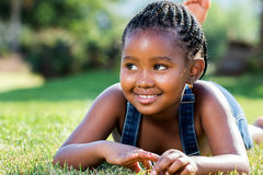 Cute african girl laying on green grass. Close up portrait of cute little african girl with braids laying on green grass Royalty Free Stock Images