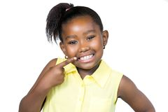 Cute african girl pointing with finger at teeth. Close up  portrait of cute little african girl with ponytail pointing with finger at teeth.Isolated on white Royalty Free Stock Photo
