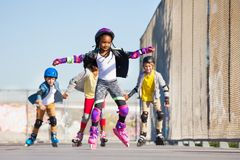 Cute African girl rollerblading at stadium. Cute African girl in protective gear rollerblading with friends at stadium outdoors at sunny day Stock Photos