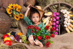 Cute  african girl sitting on straw on the background of a wooden wall Royalty Free Stock Images