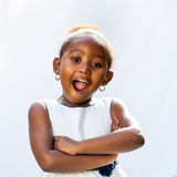 Cute african girl with surprising face expression. Portrait of cute African girl with surprising face expression. against light background Stock Photo