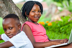 Cute african girl typing on laptop next to brother. Close up portrait of cute african girl typing on laptop next to brother under tree in park Royalty Free Stock Image