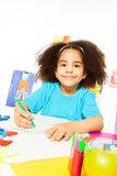 Cute African girl writing letters with pencil. On the paper while sitting at the table indoors Stock Photo