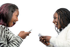 Cute african teen girls laughing with smart phones. Close up portrait of happy african teen girls laughing with smart phones. Isolated on white background Royalty Free Stock Image