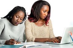Cute african teen student working on laptop with friend. stock images