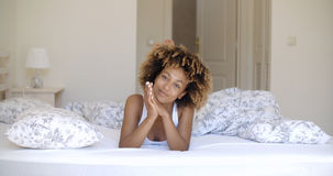 Cute african woman lying on bed and looking at camera. Royalty Free Stock Images
