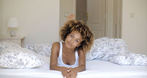 Cute african woman lying on bed and looking at camera. Stock Images